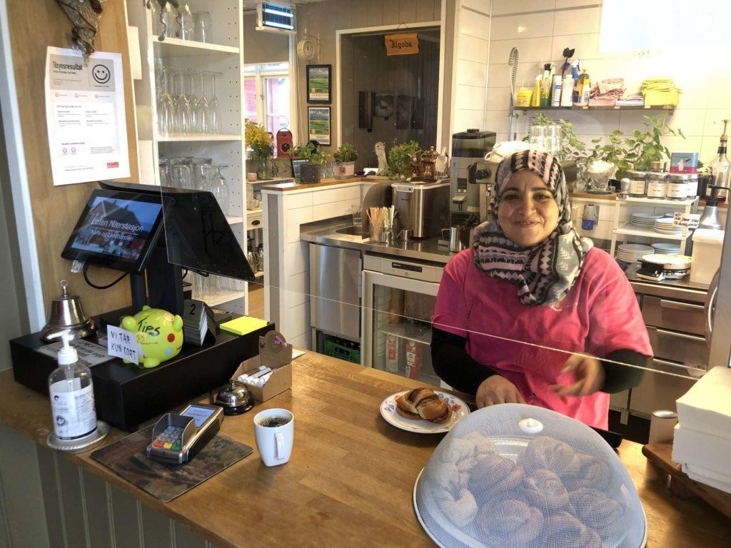 SMILENDE BAKESJEF: Rajaa Aljuhamni er bakeansvarlig på Løten Nærstasjon, men hun trør også til bak kassa når det trengs. FOTO: Marit Amundsen.