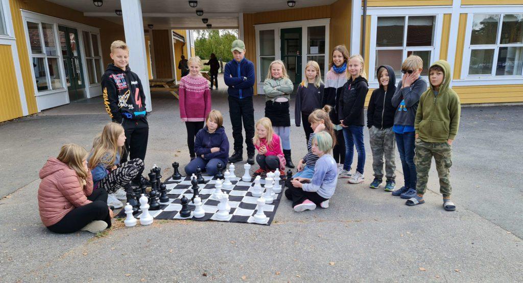 KLART TIL BRUK: Vennelek- og elevrådsrepresentanter fra 3. til 6. klasse på Ådalsbruk skole fikk overlevert sjakkbrett med store brikker som ble tatt i bruk umiddelbart.